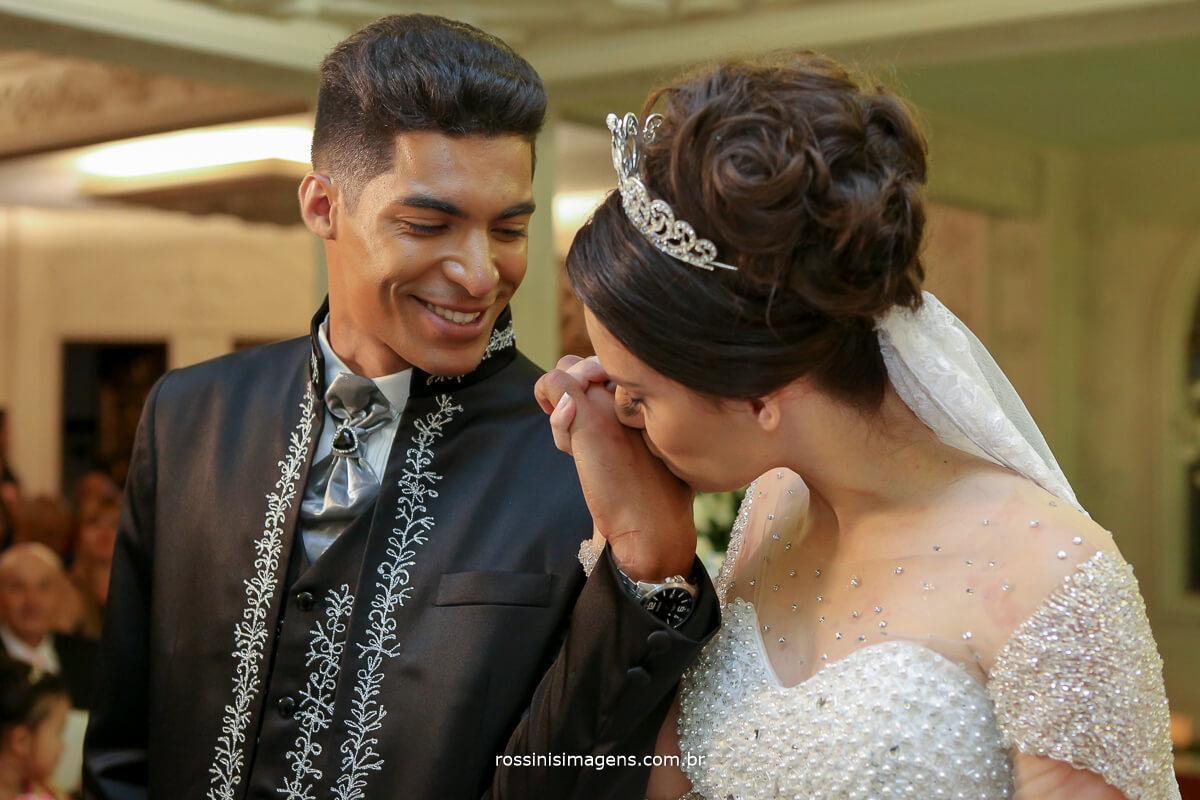noiva beijando a aliança do noivo