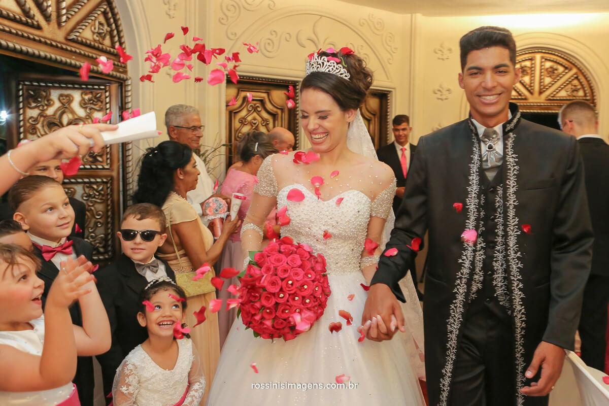 saida dos noivos do cerimonial com petalas e muito amor