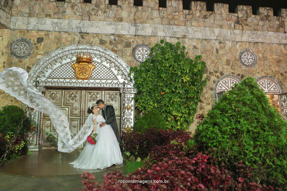 sessão de fotos apos a cerimonia noivos juntos com véu da noiva voando