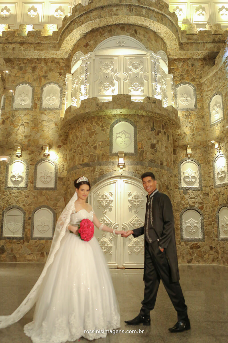 noivo dando a mão para a noiva com o cenário da realeza no maior castelo avalon