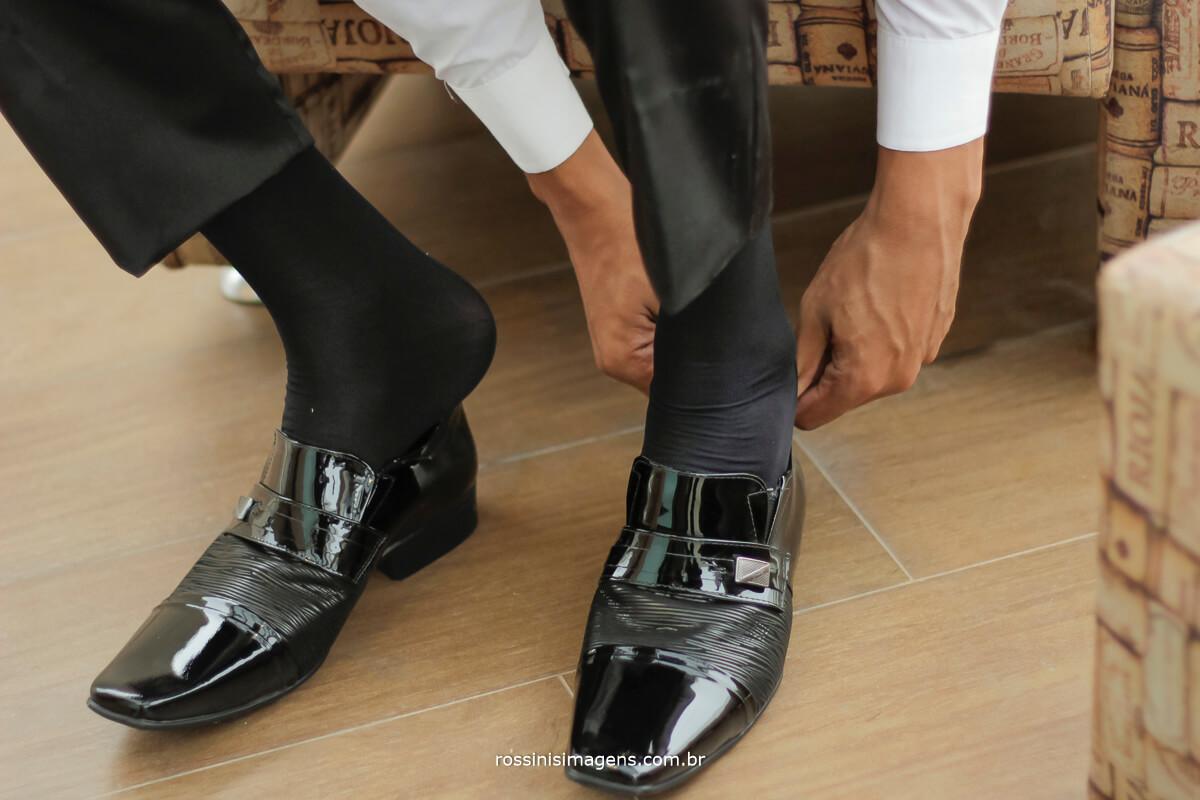 noivo colocando sapato, fotografia rossinis imagens