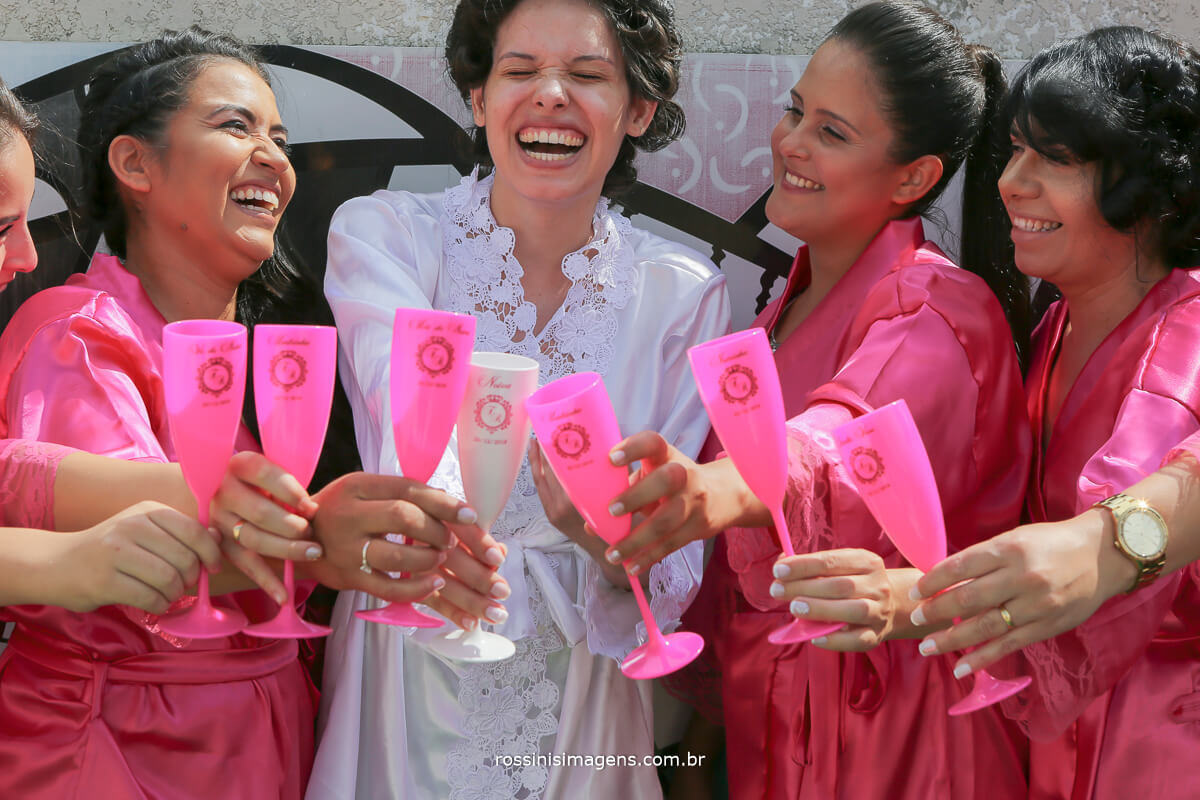 fotografia da noiva com as madrinhas de robe fazendo brinde