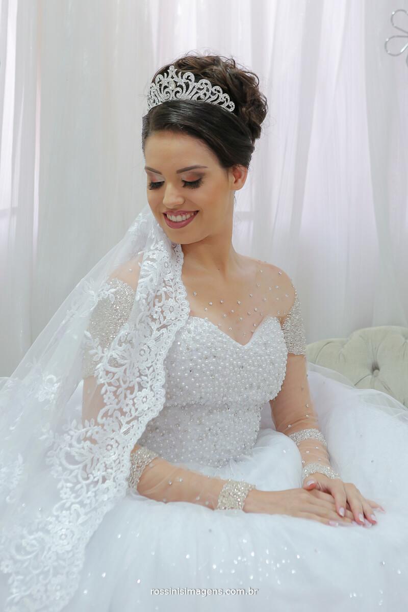 noiva sentada mostrando o véu  vestido branco