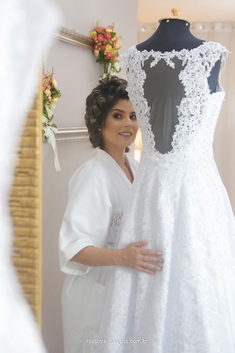 reflexo da noiva no espelho com o vestido no manequim