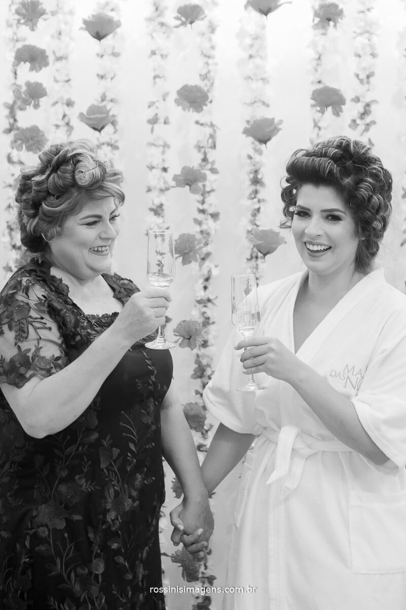 fotos preto e branco da noiva com a mae no making of brindando o casamento