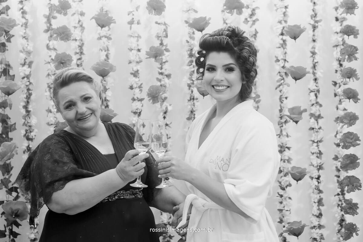 foto pb da noiva com a sogra brindando com champanhe no dia da noiva