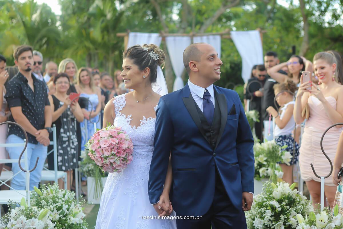 noivos na saida da cerimonia ao ar livre, casamento de dia