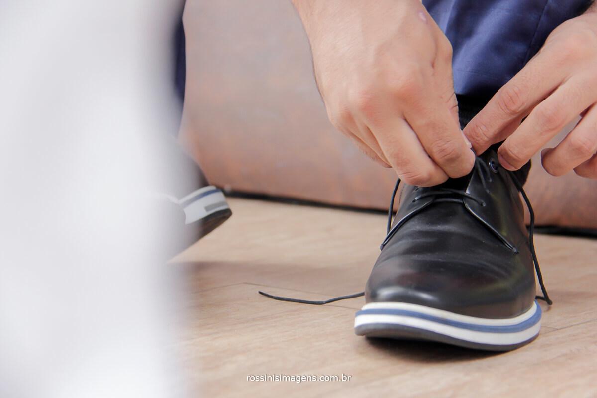 noivo colocando sapato preto com filete da cor do terno