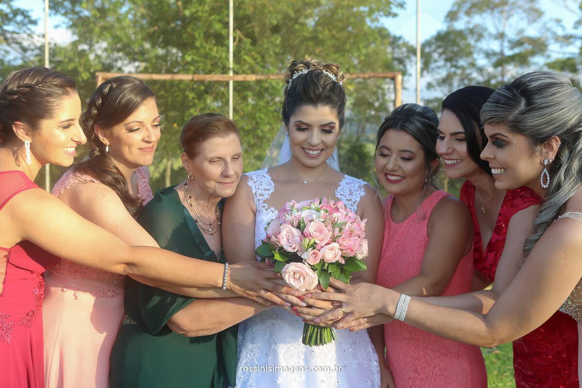 fotografia coletiva noiva e as madrinhas segurando o buquê da noiva