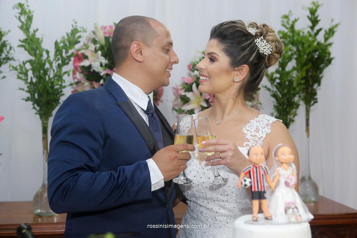 sessão de fotos dos noivos na mesa do bolo brindando com champanhe