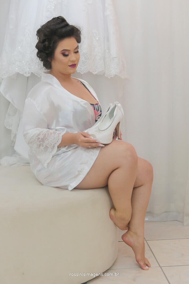 noiva de robe com o sapato ao lado do vestido