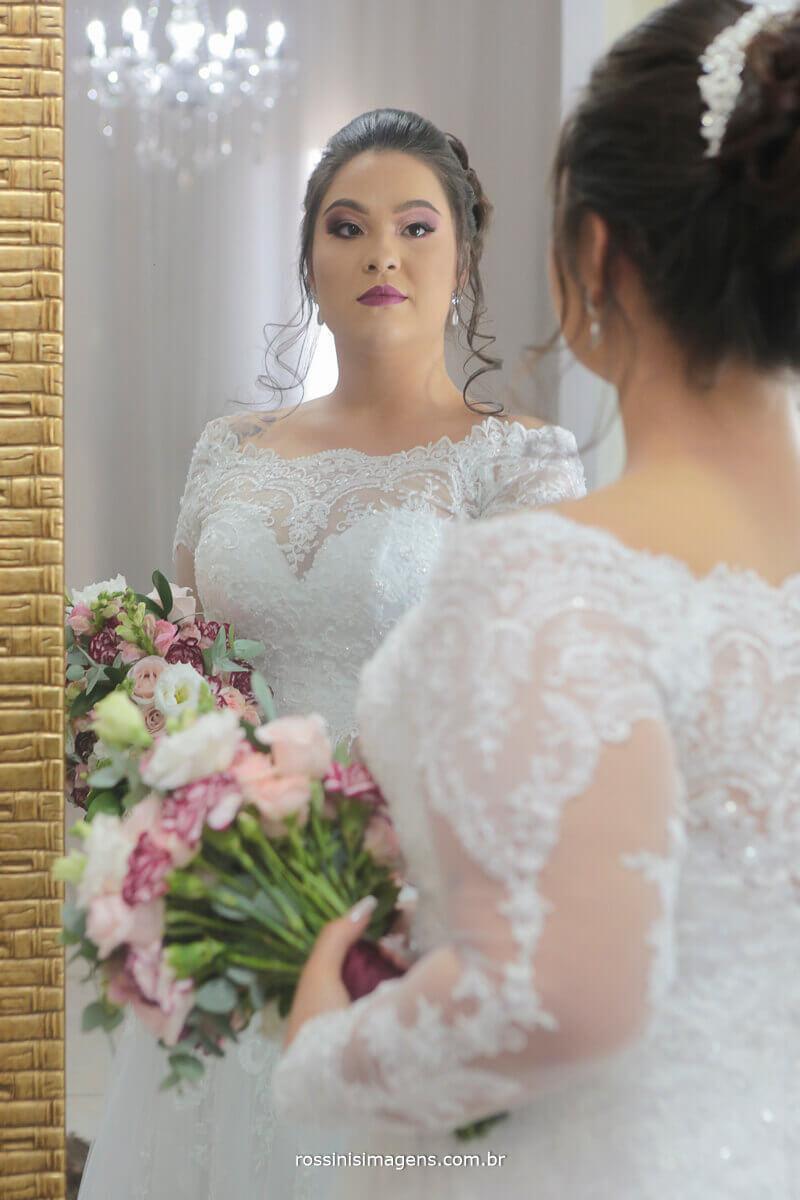noiva no espelho com o lndo buque de flores feito exclusivamente para a noivinha pela nobre decorações