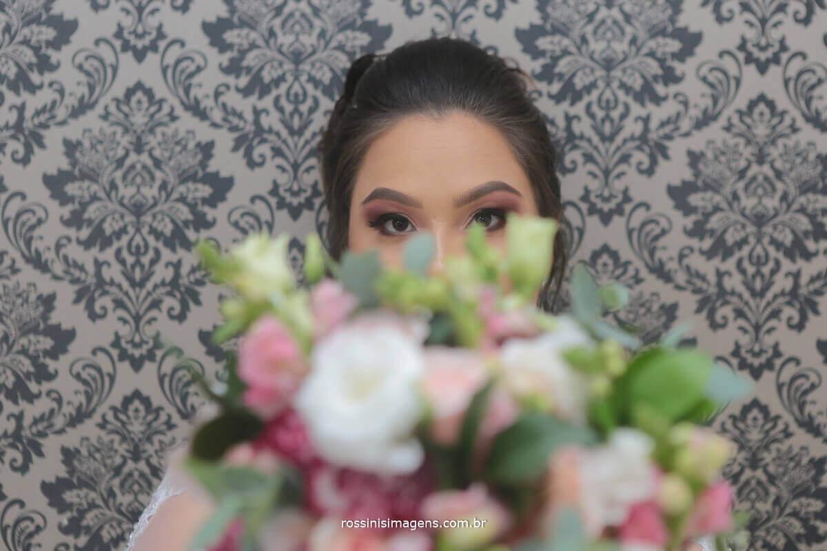 buquê na frente da noiva com um lindo e grande sorriso