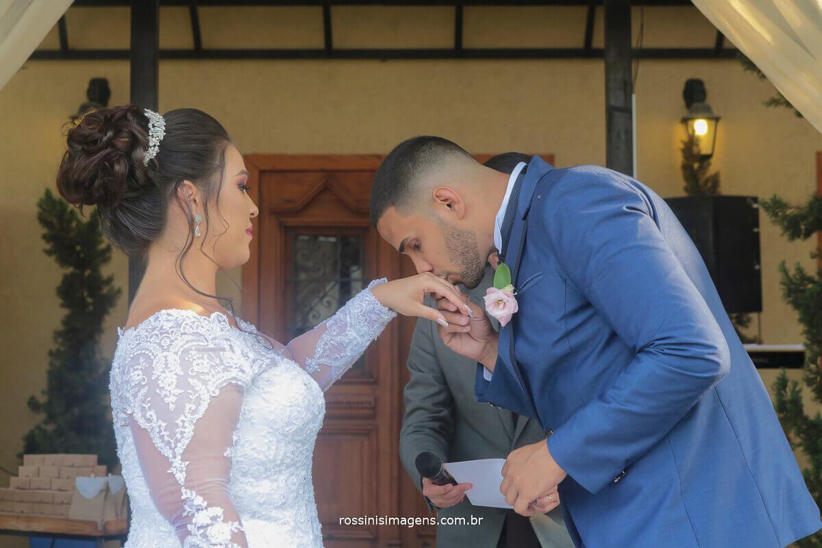 noivo beijando a aliança para com a noiva no salão di ungaro em suzano com fotografia da rossinis imagens e assessoria da debora fernandes