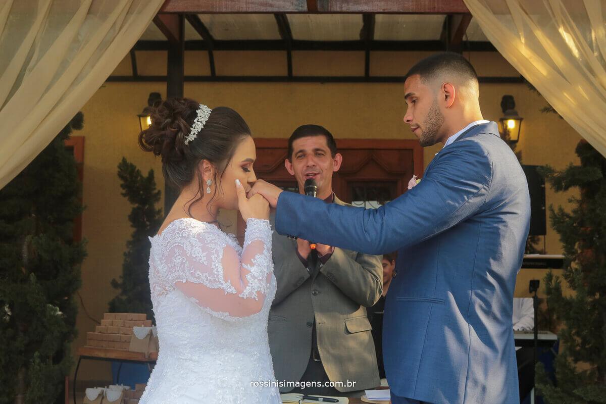 noiva beijando a aliança para com o noivo assessoria debora fernandes e fotografia da rossinis imagens