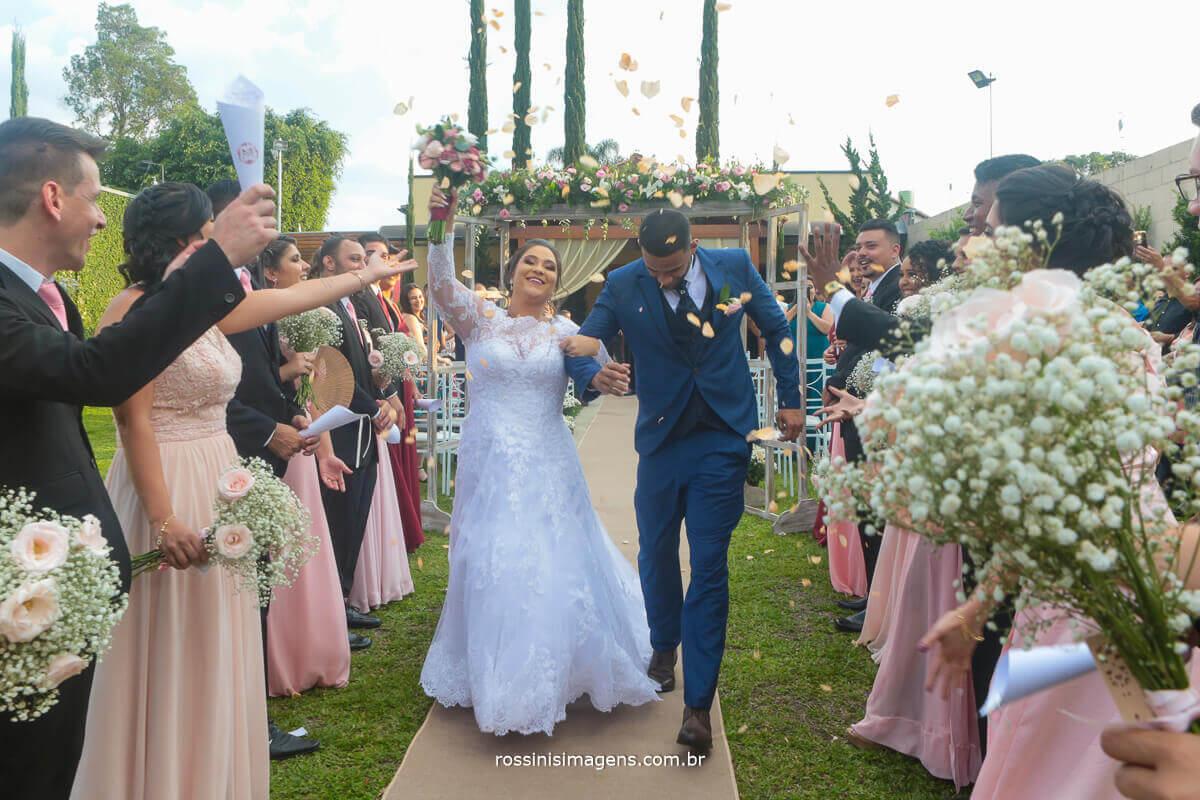saida muito animado dos noivos apos a cerimonia de casamento regada com pétalas de flores lindas