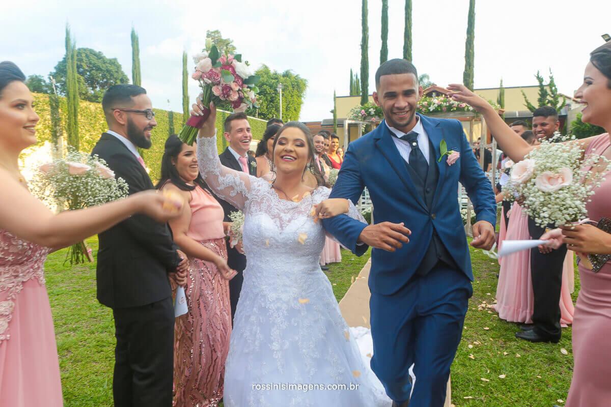 noivos animados com chuva de petalas inspirações para saida do casal apos a cerimonia de casamento