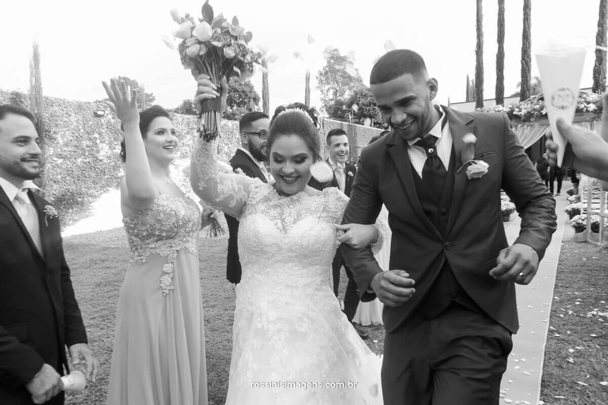 fotografia pb de casamento em saida dos noivos apos a cerimonia de casamento com os padrinhos e madrinhas rossinis imagens