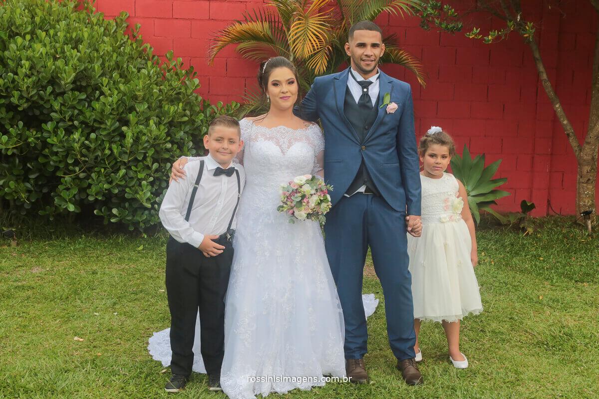 fotografia de casamento noiva e noivo com a crianças que fizeram parte do cerimonial