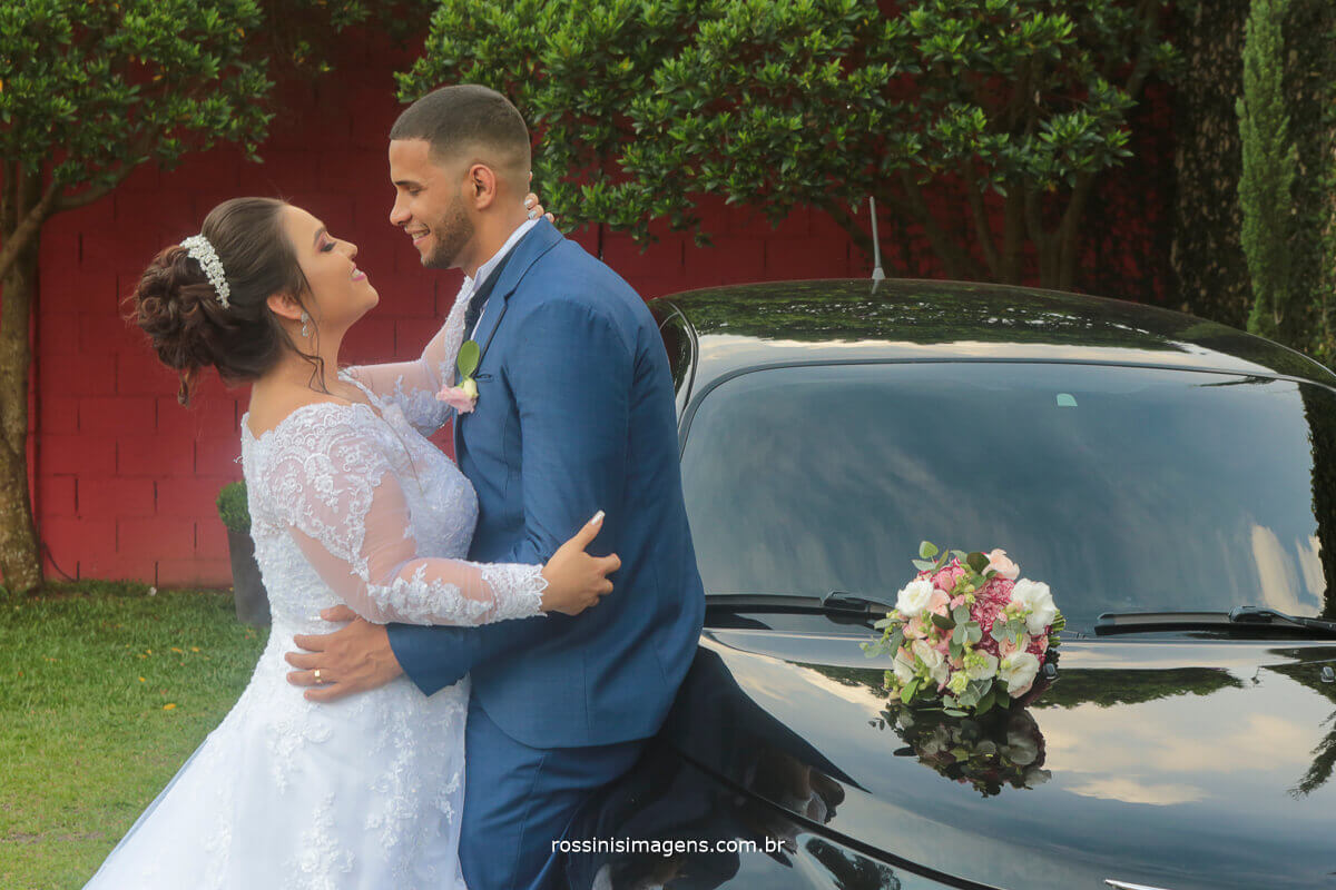 fotografia de casamento noivae noivo abraçados encostados no carro pt cruiser que trouxe a noiva para o casamento