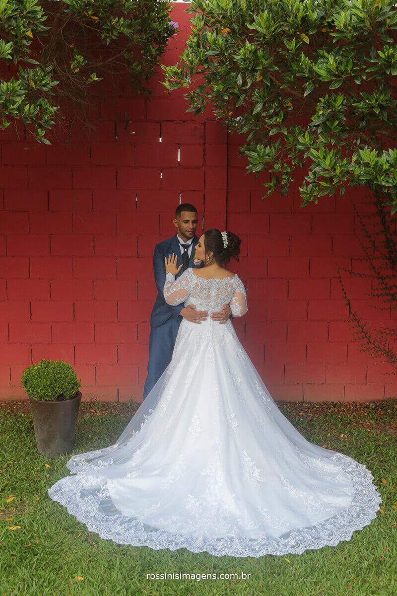 noivos abraçados mostrando os detalhes do vestido da noiva, vestido nova noiva