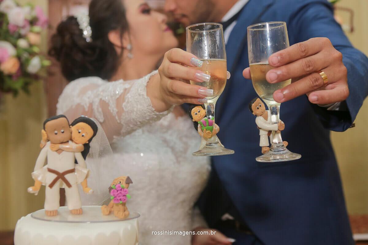 casal brindando o casamento na mesa do bolo