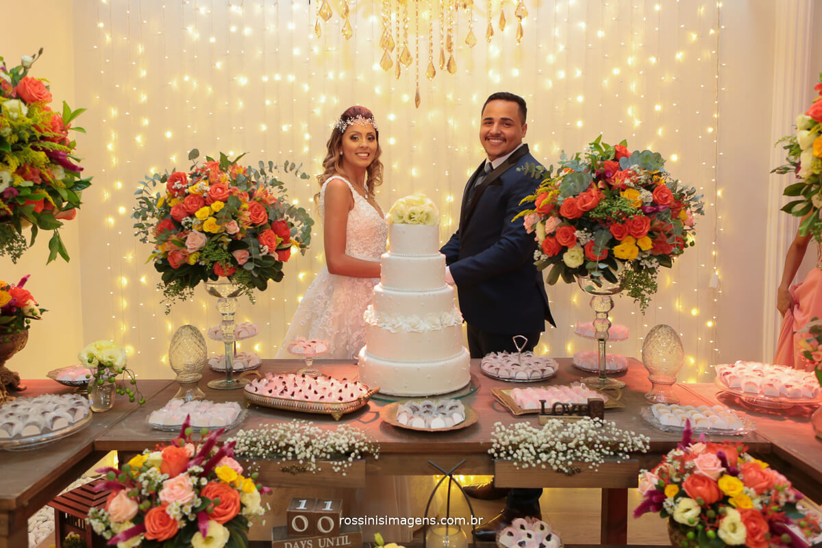 casal na mesa do bolo olhando