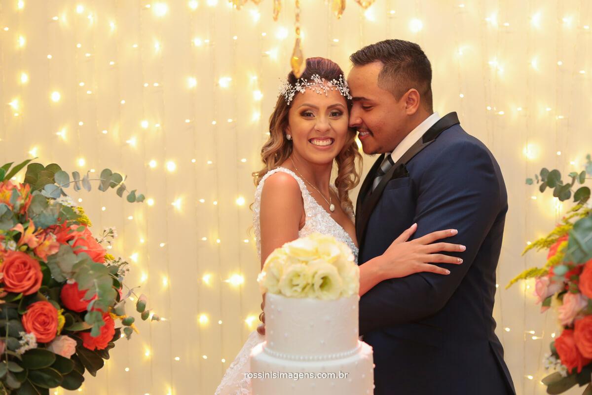 noivo abraçando noiva na mesa do bolo