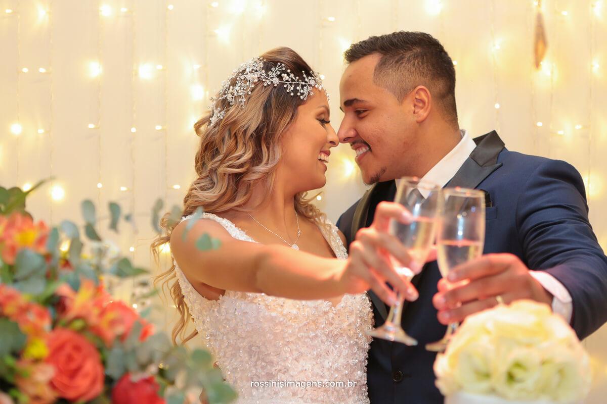 brinde dos noivos na mesa do bolo com champanhe
