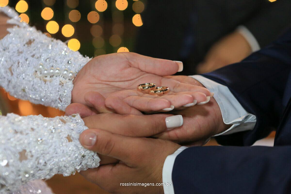 alianças de casamento Thamiris e Amauri, noivos segurando as alianças