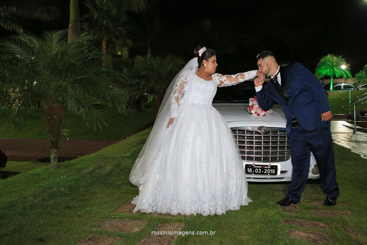 noivo beijando a noiva na frente da limousine