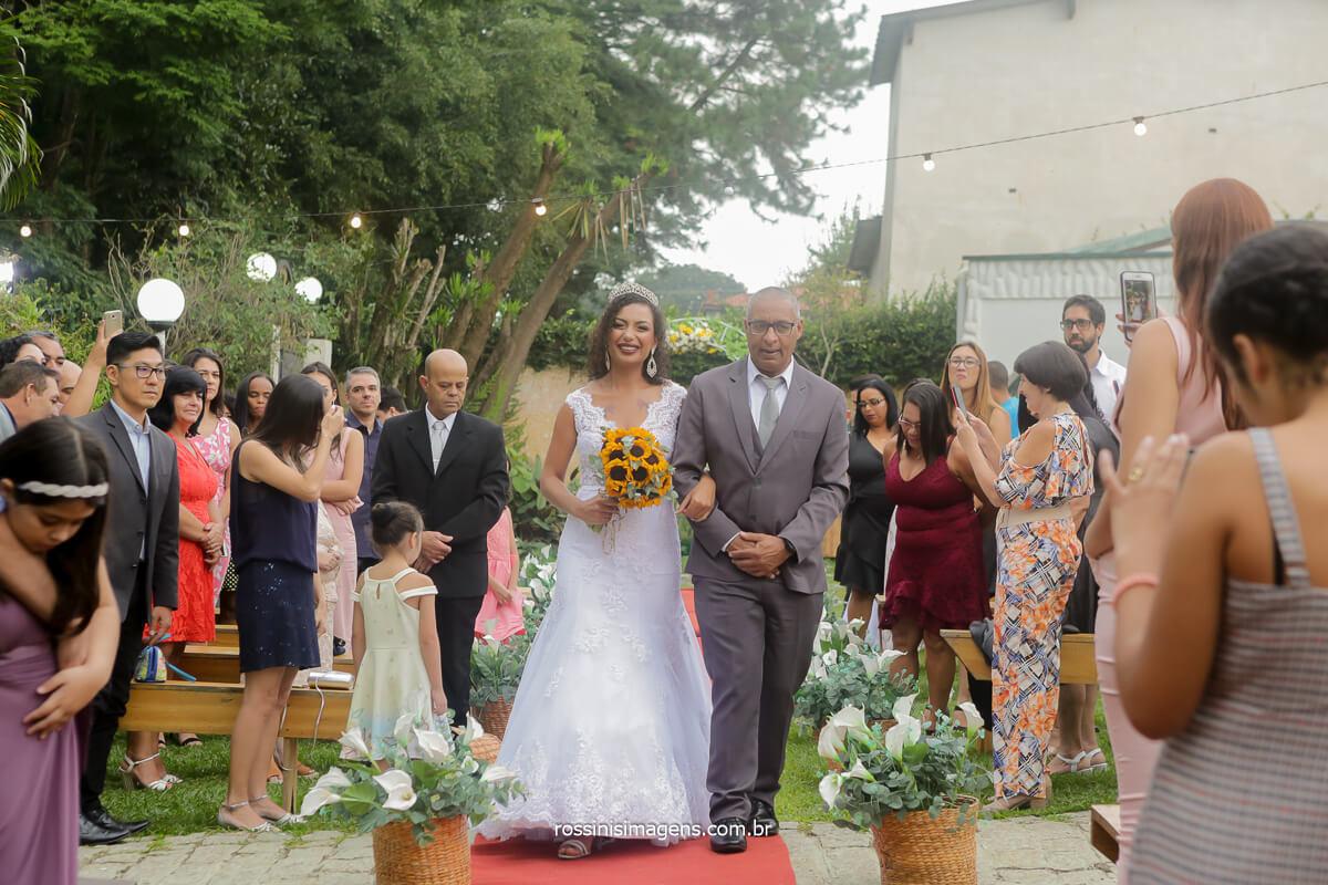entrada da noiva Patricia com o lindo buque de girassol junto com seu pai, wedding day ao ar livre