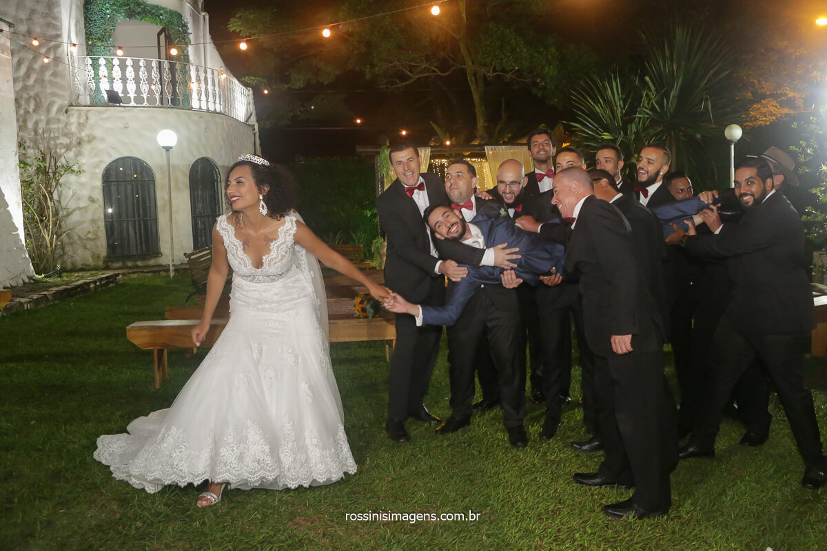fotografia coletiva noiva com os padrinhos puxando o noivo