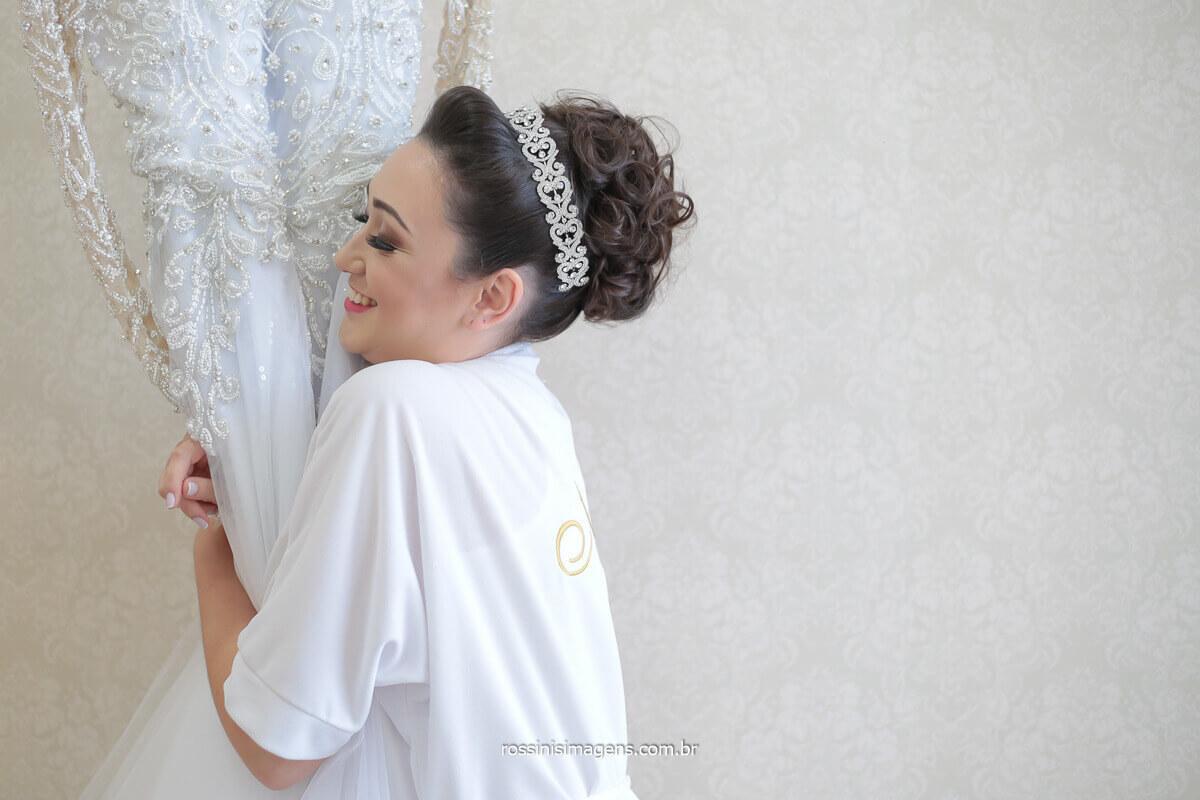 noiva apaixonada pelo lindo vestido bordado, noiva abraçando o vestido