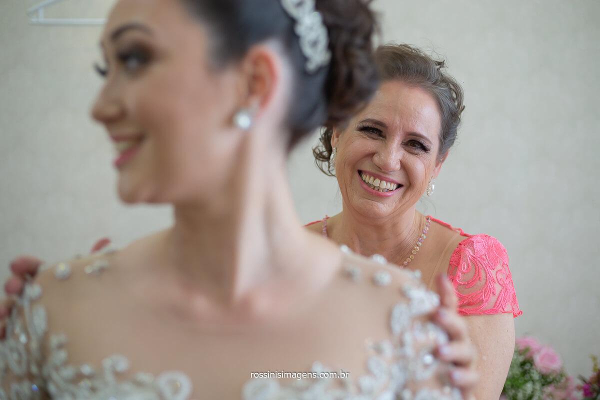 noiva sorrindo com a mãe abotoando o vestido nas costas da noiva