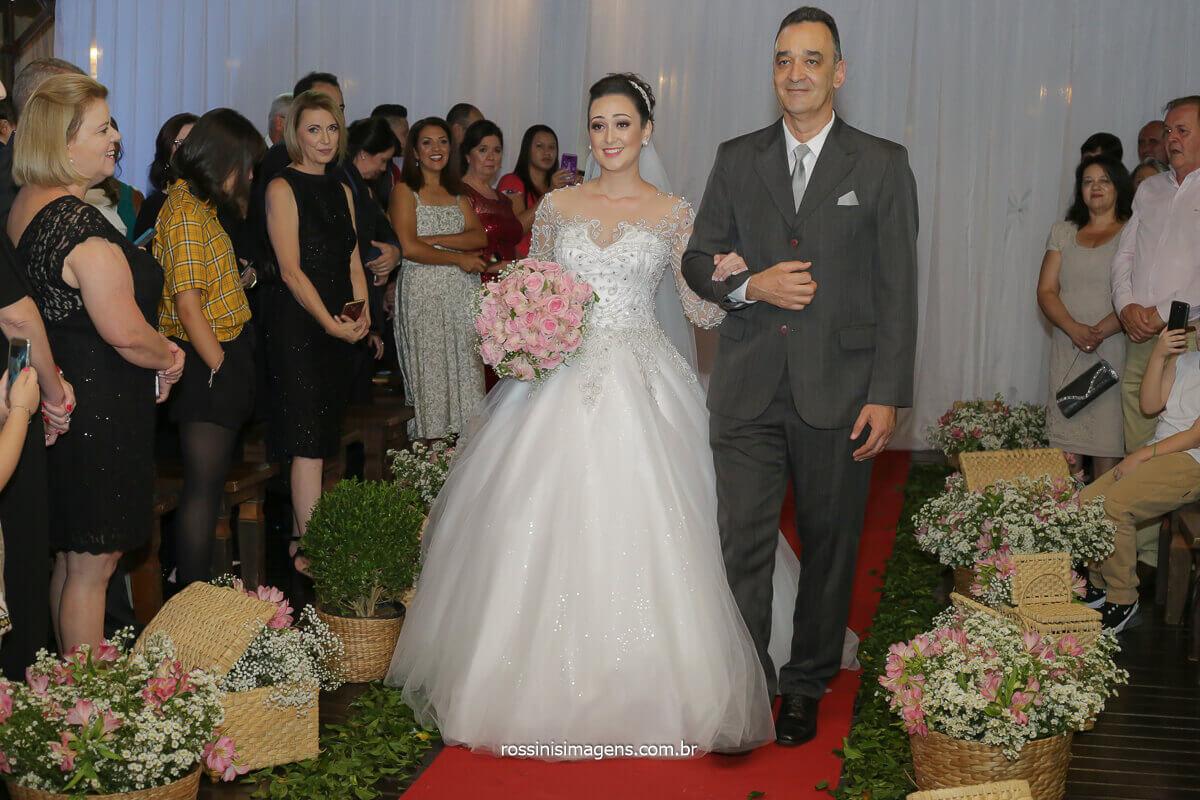 a linda e bela entrada da noiva com o pai diante do tapete vermelho conduzindo ao altar