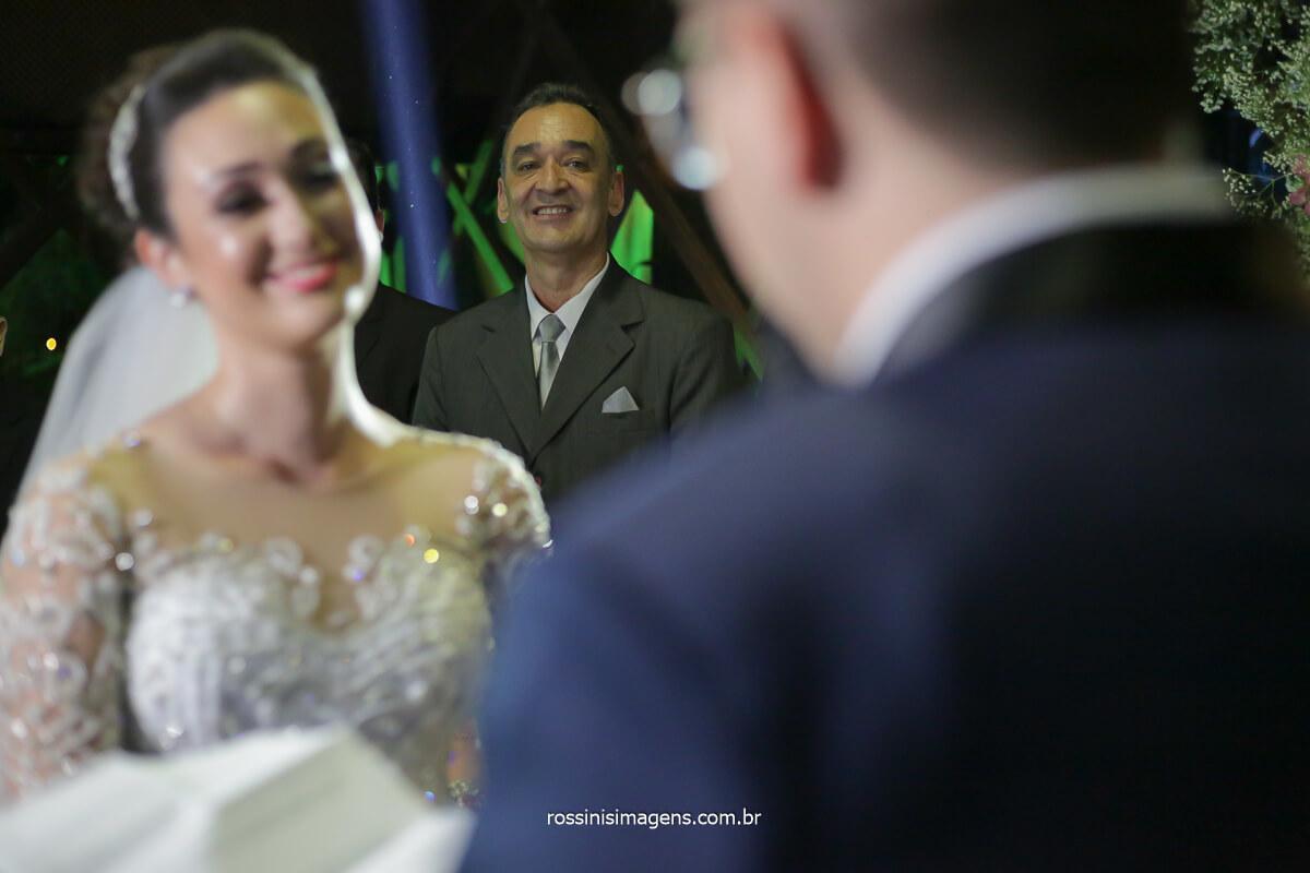 pai sorrindo ao fundo olhando para o casal, Casamento Rossinis imagens Em Mogi