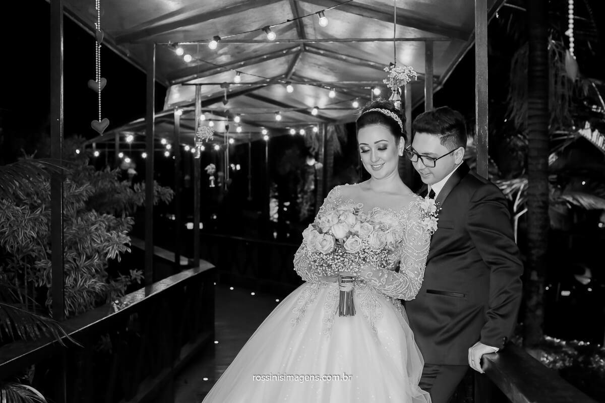 casal Josy e Daniel olhando o bouquet no corredor com luzes decorativas exclusiva no casamento