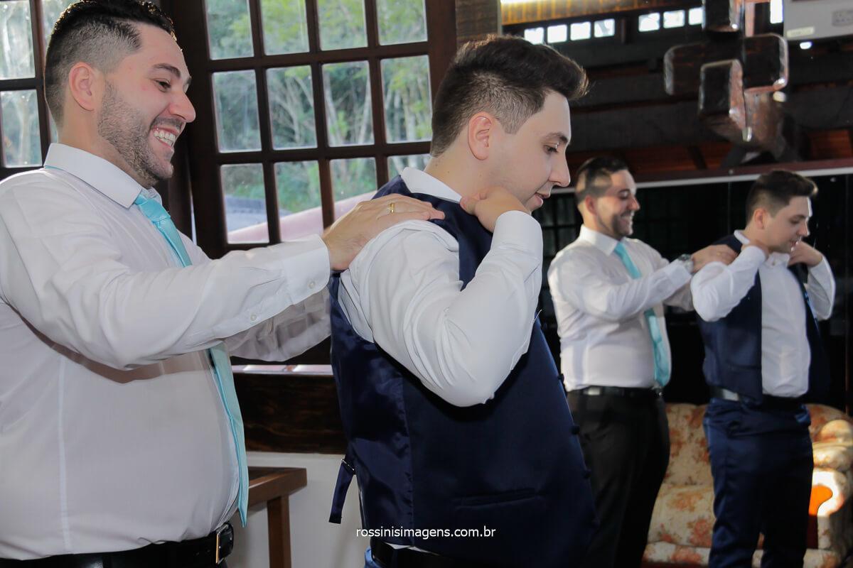 irmão do noivo ajudando a colocar a gravata no noivo, espelhos reflexos da vida família união