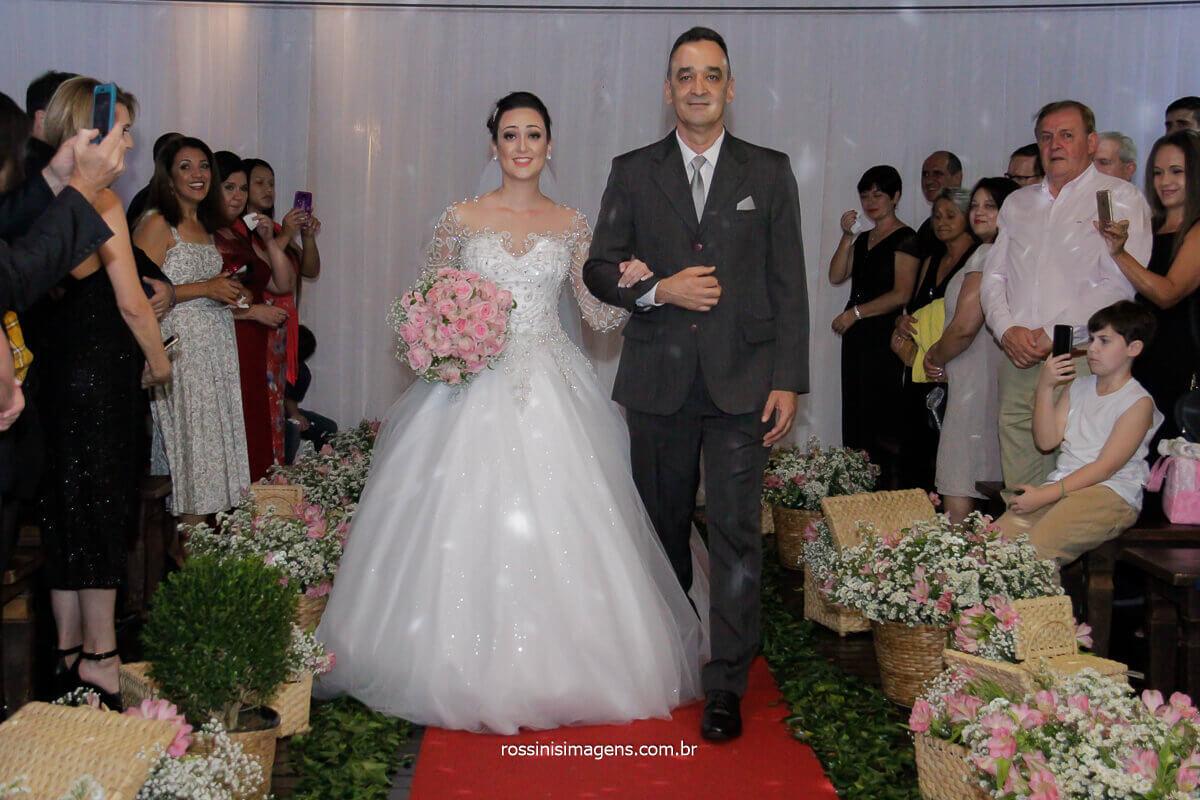 entrada da noiva josy com seu pai sendo admirada pelos convidados dia inesquecível