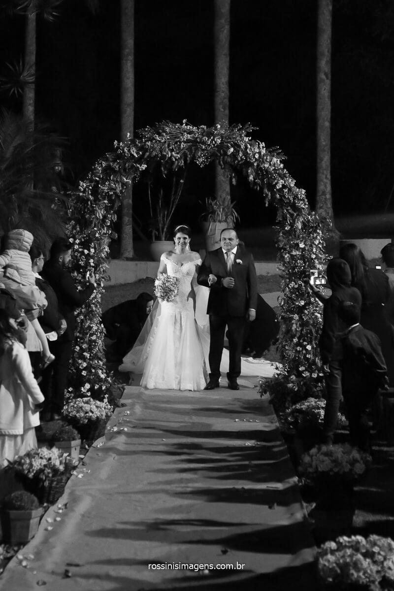 entrada da noiva junto com seu pai, passando pelo arco de flores