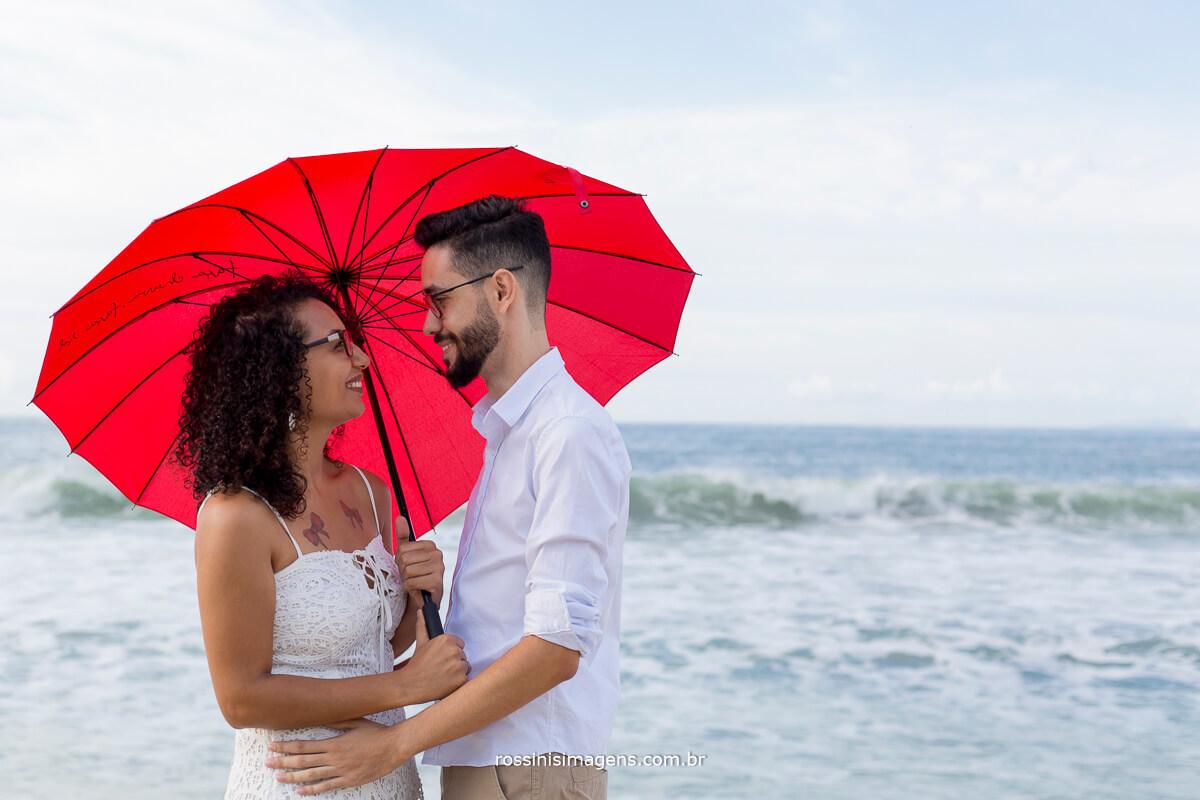 o ensaio pre casamento de Paty e Danilo, o dia lindo de sol, casal com sombrinha em formato de coração vermelho na praia o mar ao fundo @RossinisImagens
