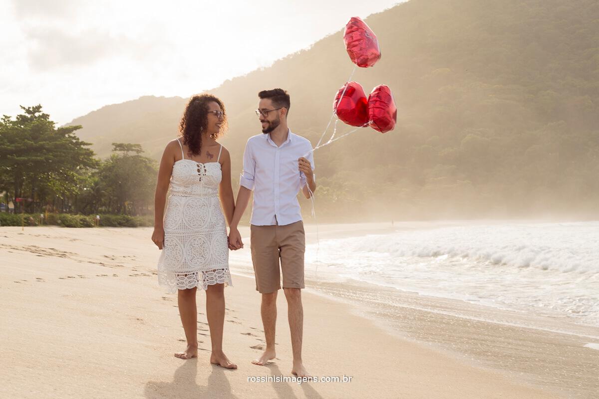 casal caminhando a beira do mar com balões de coração vermelho, @RossinisImagens