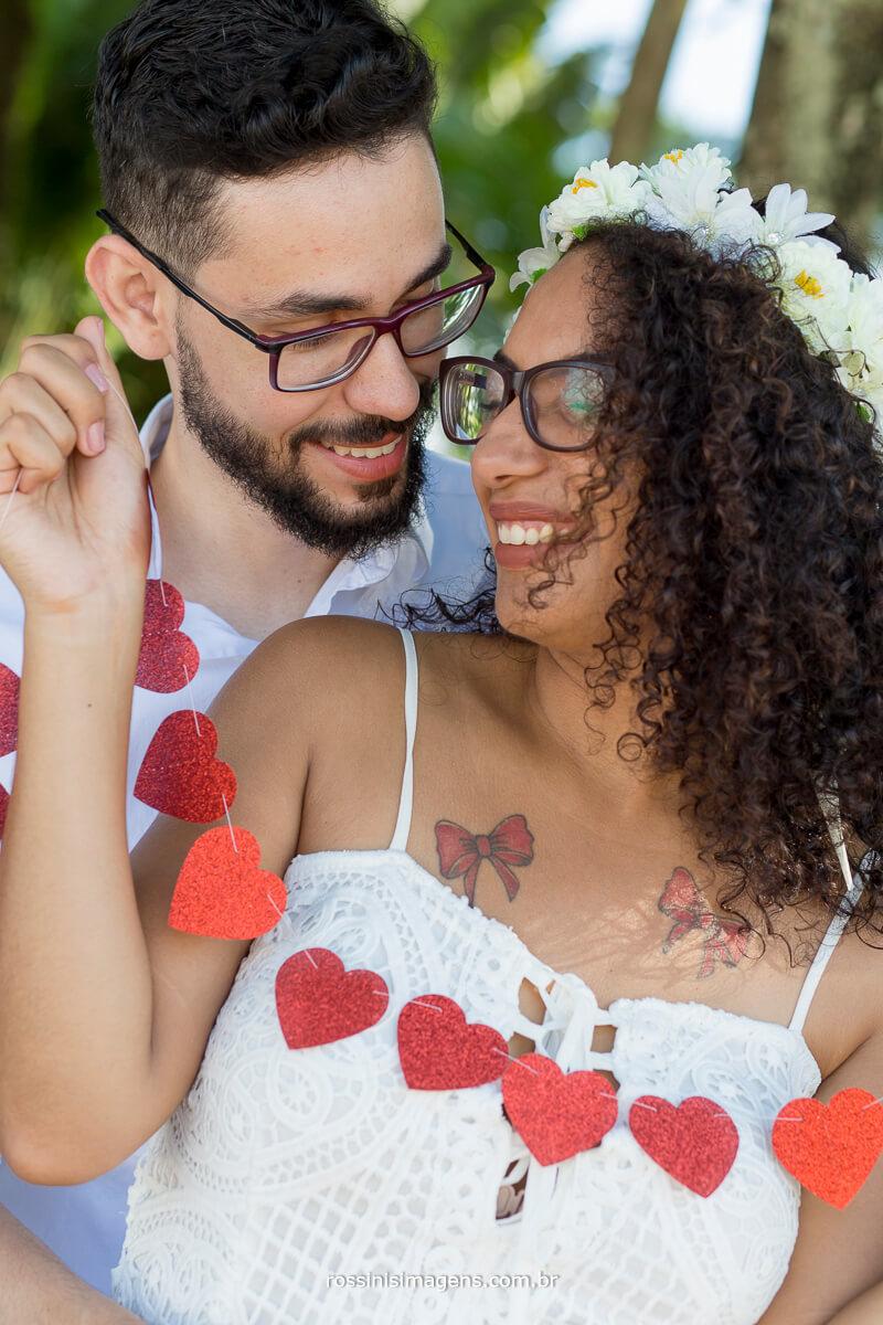 sessão de fotos de casal na praia, casal romântico com cordão de corações, @RossinisImagens