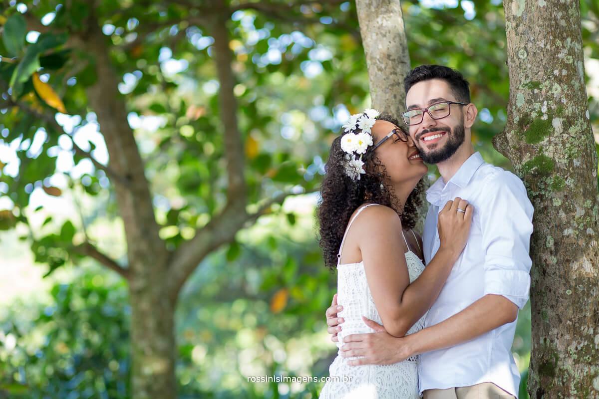 noiva abraçado ao noivo na praia com flores ao fundo, @RossinisImagens