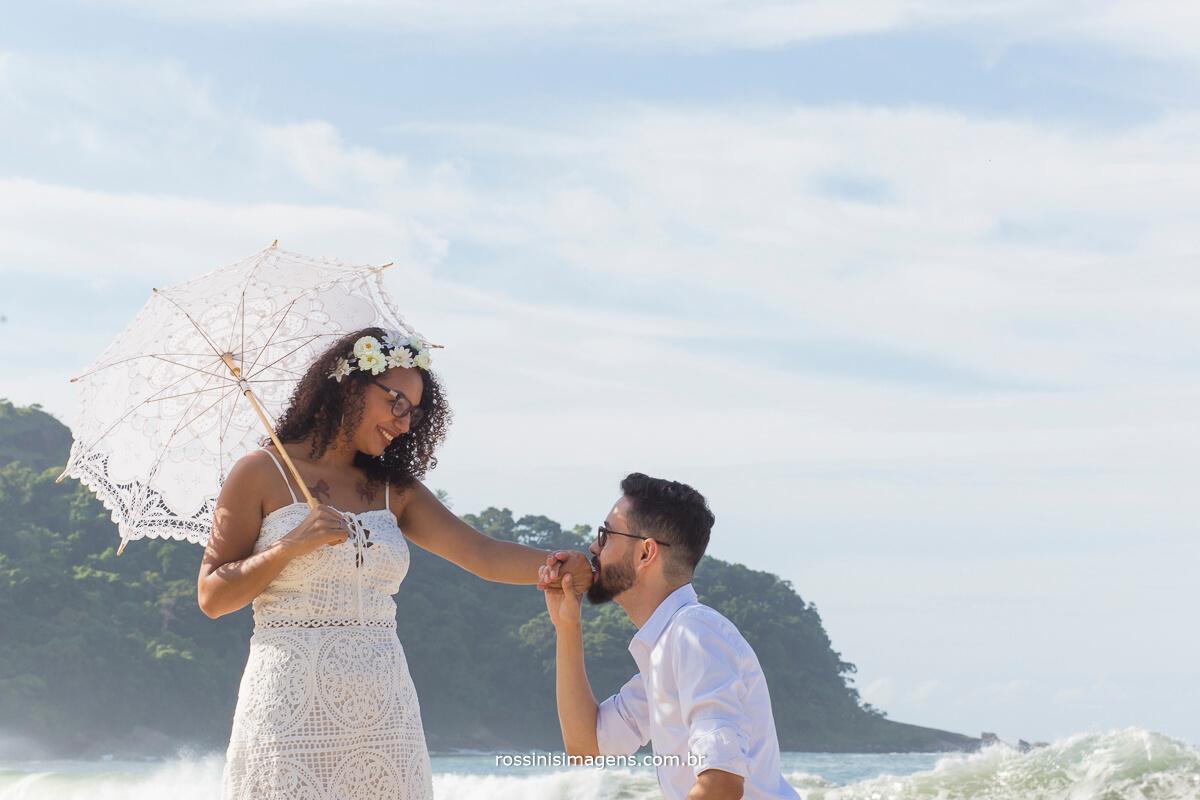 noiva com sombrinha de renda branca e noivo ajoelhado beijando a mão da noiva, ensaio na praia, viajando o mundo, @RossinisImagens