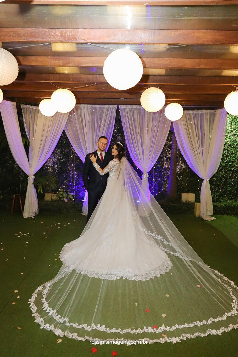 noiva e noivo um de frente pára o outro e noiva mostrando todos os detalhes do vestido na parte das costas, fotografo de casamento @RossinisImagens