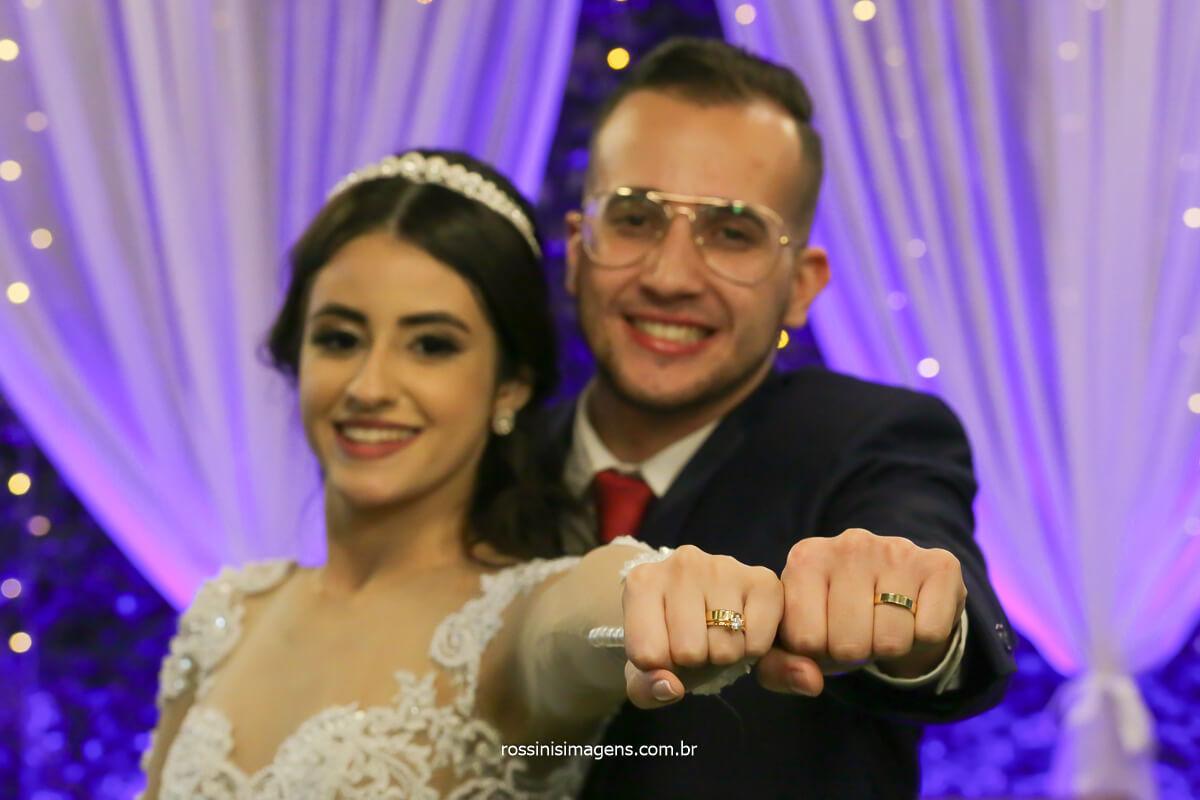 noivos Larissa e Filipe exibindo as aliança com o braço esticado para frente, fotografo de casamento @RossinisImagens