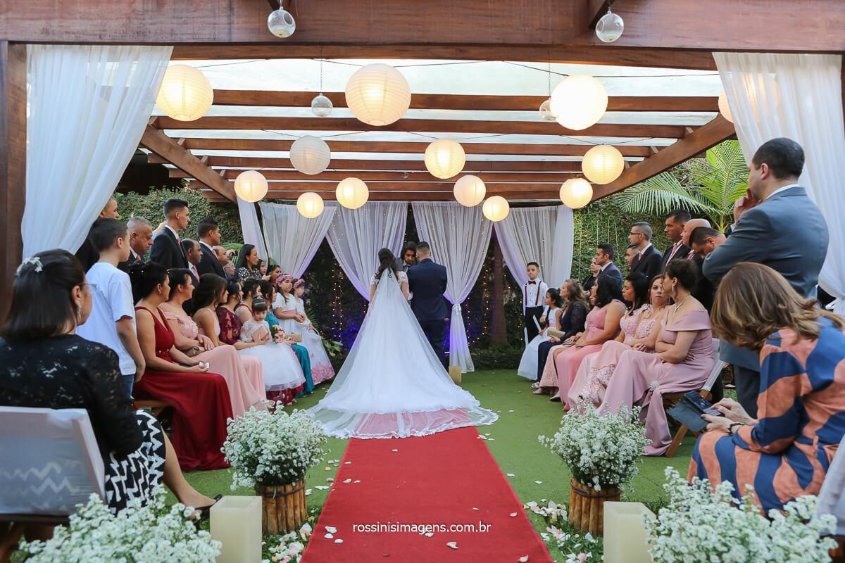 casamento acontecendo no espaço fagundes com o cerimonialista Luciano Toledo noivos no altar e vestido da noiva arrumado de costa, fotografo de casamento @RossinisImagens