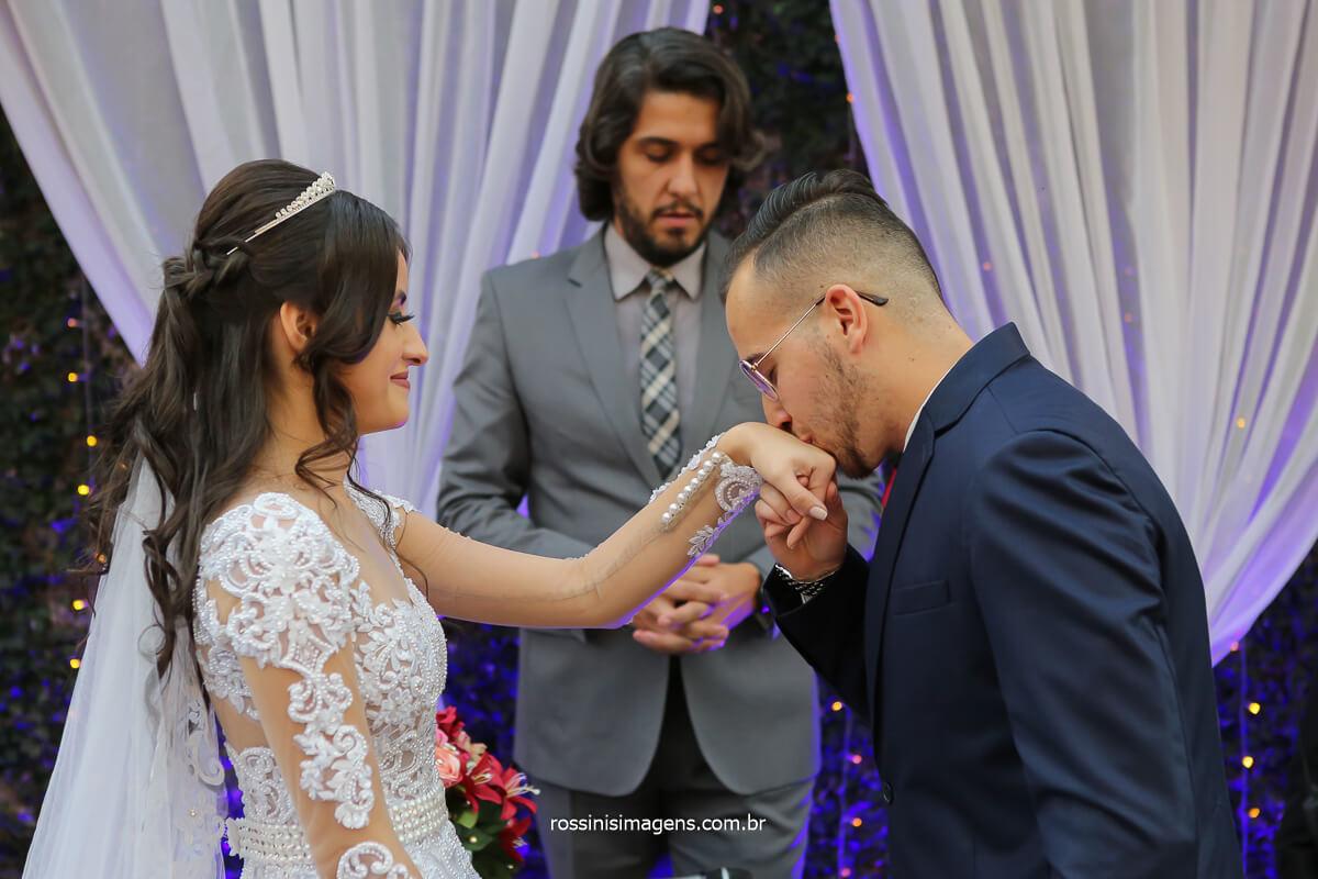 noivo coloca aliança na mão esquerda da noiva e deu um beijo na aliança, fotografo de casamento @RossinisImagens